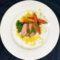 Pato a la naranja sobre reducción cítrica y cama de vegetales salteados